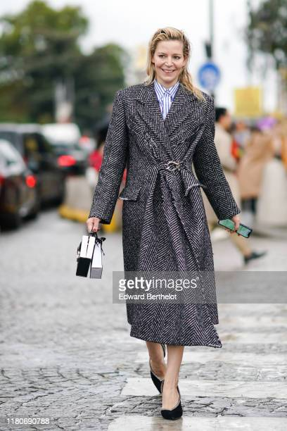 A guest wears a blue and white striped shirt a black and white striped coat outside Chanel during Paris Fashion Week Womenswear Spring Summer 2020 on...