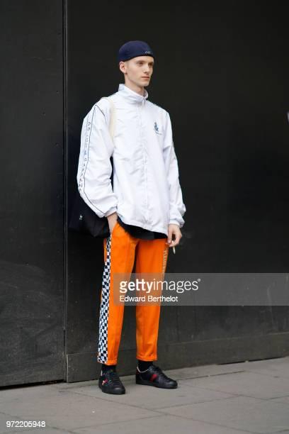A guest wears a blue beanie hat a Dolce Gabbana white sportswear jacket orange pants black Gucci sneakers during London Fashion Week Men's June 2018...