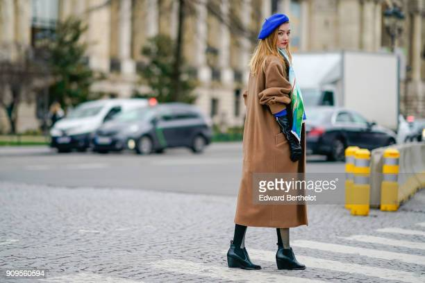 A guest wears a blue beret hat a camel coat a color scarf outside Chanel during Paris Fashion Week Haute Couture Spring/Summer 2018 on January 23...