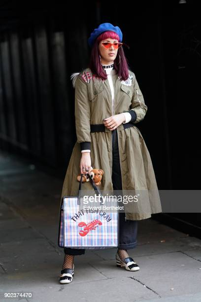 A guest wears a blue beret hat red glasses a green khaki coat a bag 'that fish cray' with a printed lobster during London Fashion Week Men's January...