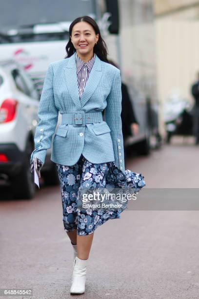 A guest wears a blue blazer jacket a striped shirt a flower print skirt and white boots outside the Hermes show during Paris Fashion Week Womenswear...