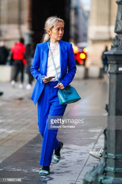 A guest wears a blue blazer jacket a white lace mesh embroidered top a blue bag blue pants shoes outside Louis Vuitton during Paris Fashion Week...