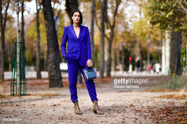 A guest wears a blue blazer jacket blue pants snake print shoes outside Akris during Paris Fashion Week Womenswear Spring/Summer 2019 on September 30...
