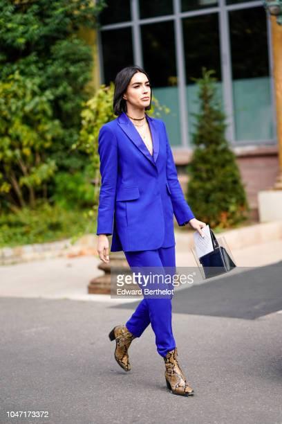 A guest wears a blue blazer jacket blue pants snake print shoes outside Akris during Paris Fashion Week Womenswear Spring/Summer 2019 on September 30...