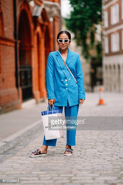 A guest wears a blue blazer jacket blue pants white sunglasses sandals during London Fashion Week Men's June 2018 on June 09 2018 in London England