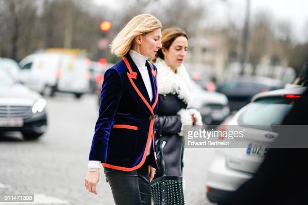 A guest wears a blue blazer velvet jacket with red lines black leather pants black leather shoes outside Chanel during Paris Fashion Week Haute...