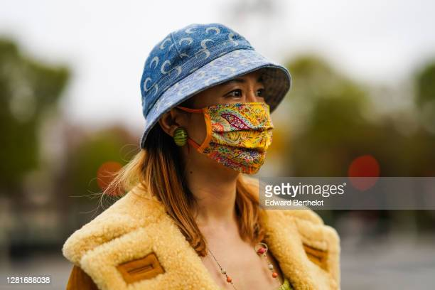 Guest wears a blue bob hat, a yellow floral print protective face mask, green watermelon earrings, a brown coat, outside Chanel, during Paris Fashion...