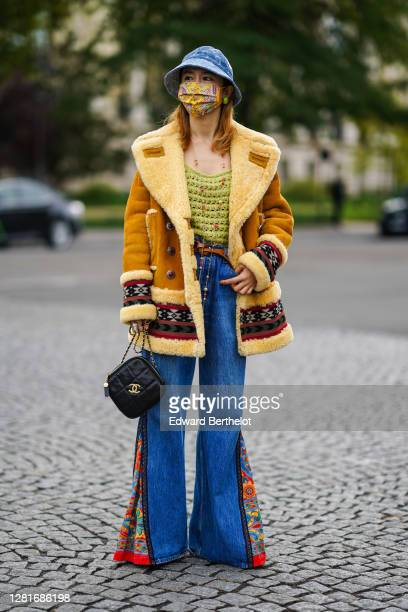 Guest wears a blue bob hat, a yellow floral print protective face mask, green watermelon earrings, a brown long aviator coat with inner lining made...