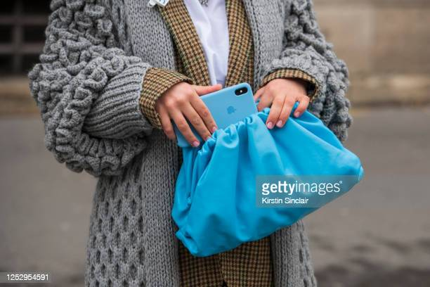 Guest wears a blue Bottega Veneta bag and a blue iphone with a grey chunky cable knit cardigan, white shirt and a tweed jacket on March 02, 2020 in...