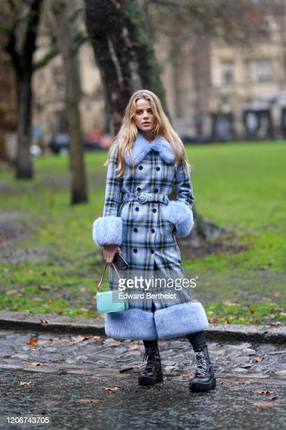 A guest wears a blue checked long coat with fluffy parts a turquoise bag a belt black boots leggings during London Fashion Week Fall Winter 2020 on...