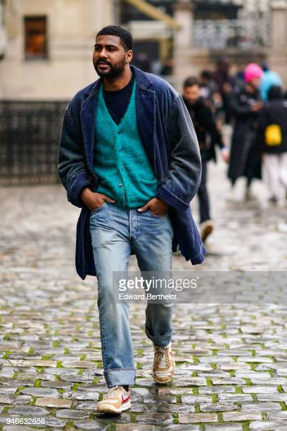 A guest wears a blue coat a blue jacket blue jeans brown Nike sneakers shoes outside Thom Browne during Paris Fashion Week Menswear Fall Winter...