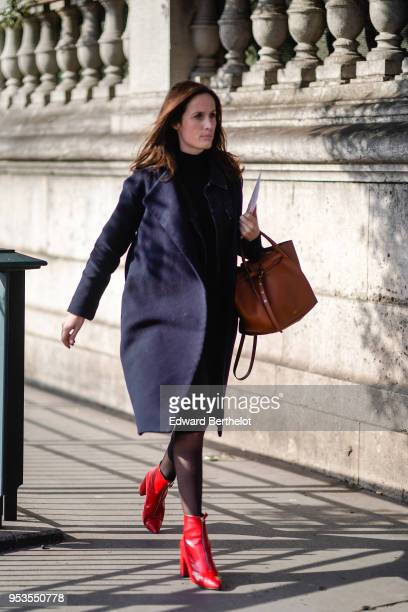 Guest wears a blue coat, a brown bag, redd leather shoes, during Paris Fashion Week Womenswear Fall/Winter 2018/2019, on February 28, 2018 in Paris,...