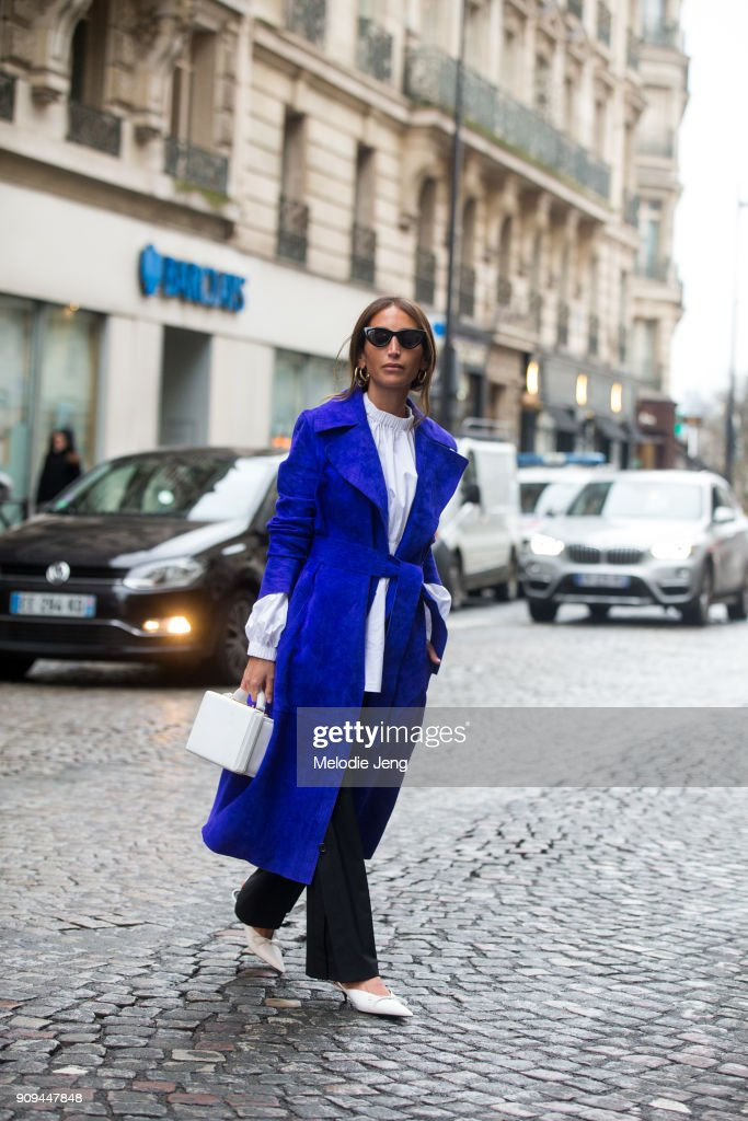 A guest wears a blue coat and white shirt, rectangular bag, and shoes outside the Alexis Mabille show at Salle Pleyel on January 23, 2018 in Paris, France.