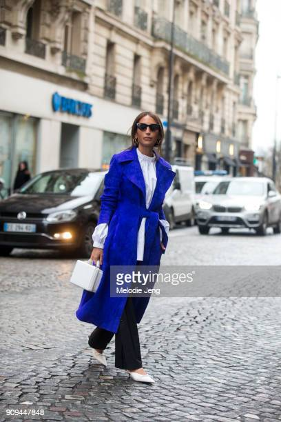 A guest wears a blue coat and white shirt rectangular bag and shoes outside the Alexis Mabille show at Salle Pleyel on January 23 2018 in Paris France