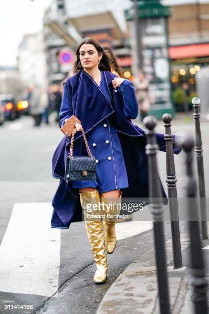 A guest wears a blue coat with a cape gold buttons a chanel bag gold shiny thigh high boots outside Alexis Mabille during Paris Fashion Week Haute...