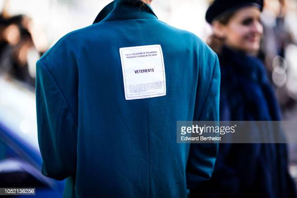 A guest wears a blue coat with a 'VETEMENTS' patch outside Haider Ackermann during Paris Fashion Week Womenswear Spring/Summer 2019 on September 29...