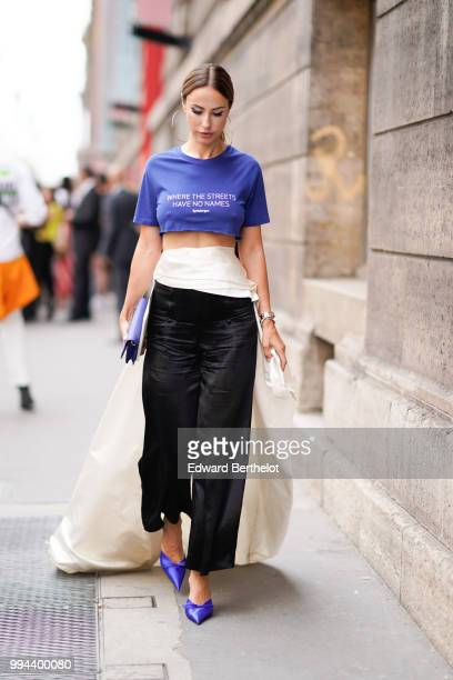 A guest wears a blue cropped bare belly tshirt with the printed sentence where the streets have no names a white skirt black flared pants blue shoes...