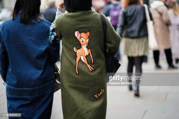 A guest wears a blue denim coat a guest wears a green coat with a Bambi design on the back during London Fashion Week February 2019 on February 19...