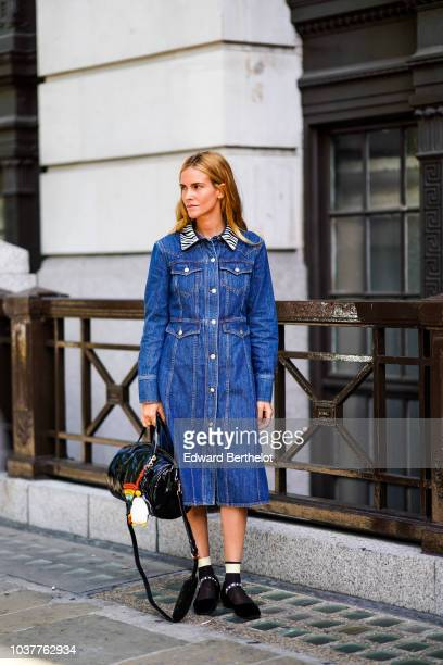 A guest wears a blue denim dress a black bag during London Fashion Week September 2018 on September 15 2018 in London England