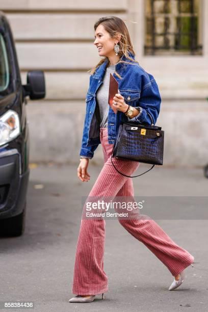 A guest wears a blue denim jacket a crocodile black leather bag a gray top pink flare pants outside Moncler during Paris Fashion Week Womenswear...