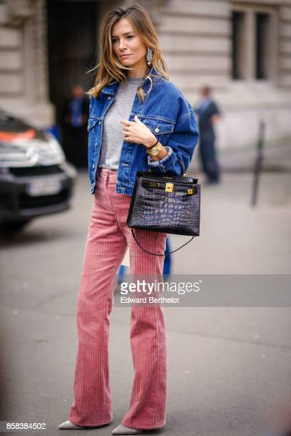 A guest wears a blue denim jacket a crocodile black leather bag a gray top pink flare pants outside Moncler during Paris Fashion Week Womenswear...