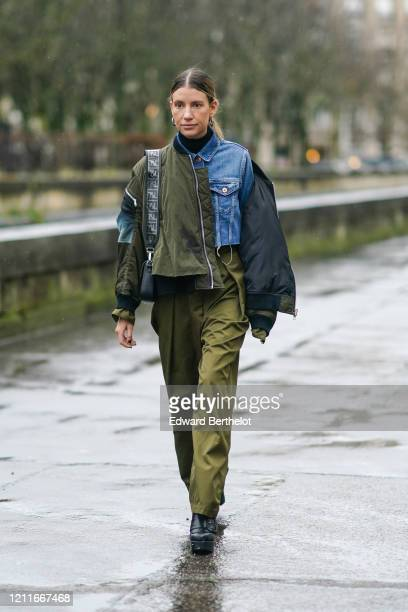 Guest wears a blue denim jacket, a green khaki bomber jacket with black inner lining, a Fendi bag, flared pants, black leather shoes, earrings,...