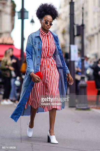 A guest wears a blue denim jacket a red striped dress white shoes outside Moncler during Paris Fashion Week Womenswear Spring/Summer 2018 on October...