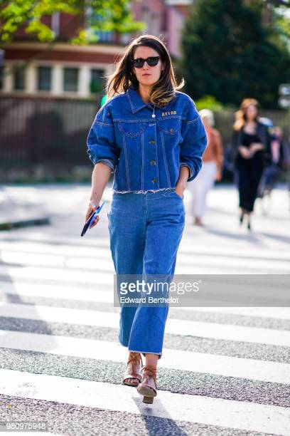 A guest wears a blue denim jacket blue denim flared pants outside Dries Van Noten during Paris Fashion Week Menswear SpringSummer 2019 on June 21...
