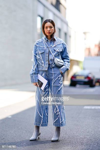 A guest wears a blue denim jacket flared pants a blue semi circular bag during London Fashion Week Men's June 2018 on June 10 2018 in London England
