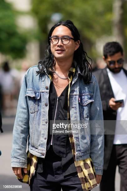 A guest wears a blue denim jacket outside Rick Owens during Paris Fashion Week Menswear SpringSummer 2019 on June 21 2018 in Paris France
