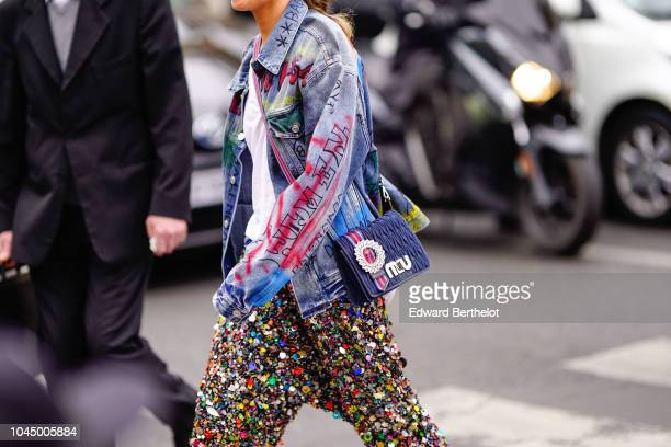 A guest wears a blue denim jacket with printed graffiti a blue Miu Miu bag pants with embroidered colored pearls white shoes outside Miu Miu during...