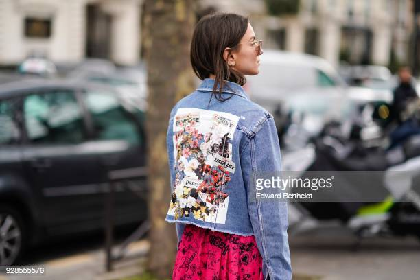 A guest wears a blue denim jacket with prints outside Miu Miu during Paris Fashion Week Womenswear Fall/Winter 2018/2019 on March 6 2018 in Paris...