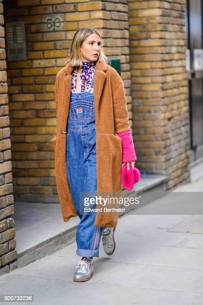A guest wears a blue denim jumpsuit a brown fluffy coat silver shoes during London Fashion Week February 2018 on February 17 2018 in London England