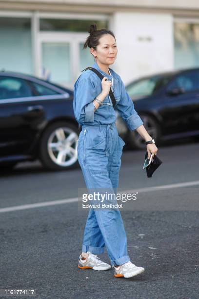 A guest wears a blue denim outfit with sneakers outside Acne during Paris Fashion Week Haute Couture Fall/Winter 2019/2020 on June 30 2019 in Paris...