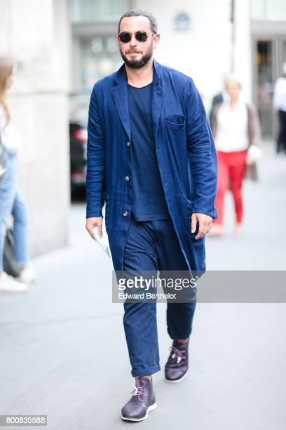 A guest wears a blue denim oversized shirt a blue tshirt blue pants purple shoes sunglasses outside the Hermes show during Paris Fashion Week...