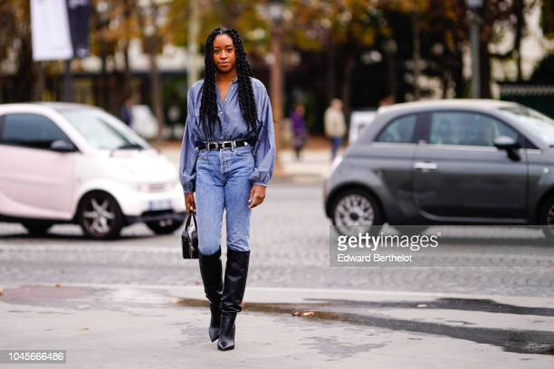 Guest wears a blue denim shirt, a leather belt, blue jeans, black leather boots, outside Chanel, during Paris Fashion Week Womenswear Spring/Summer...