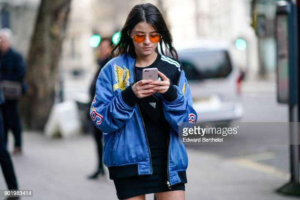 A guest wears a blue Diesel bomber jacket with a printed eagle logo 'wild spirit' orange clear sunglasses black short and is sending a text message...