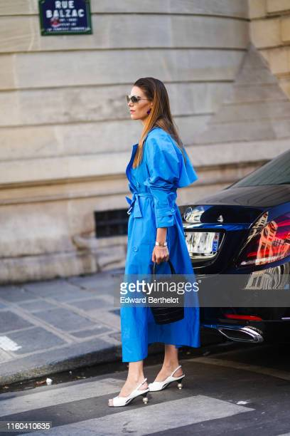 A guest wears a blue dress a black bag white shoes outside Valentino during Paris Fashion Week Haute Couture Fall/Winter 2019/2020 on July 03 2019 in...