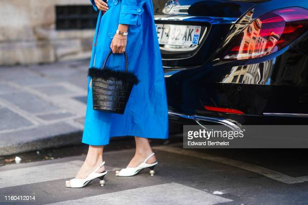 A guest wears a blue dress a fluffy black bag white shoes outside Valentino during Paris Fashion Week Haute Couture Fall/Winter 2019/2020 on July 03...