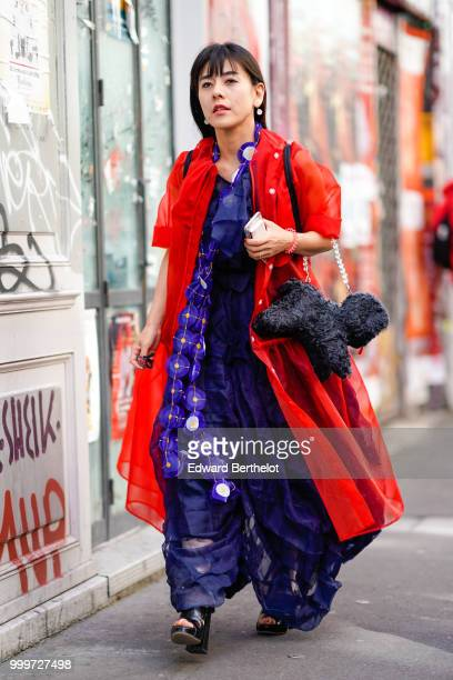 A guest wears a blue dress and a red coat outside Yohji Yamamoto during Paris Fashion Week Menswear SpringSummer 2019 on June 21 2018 in Paris France
