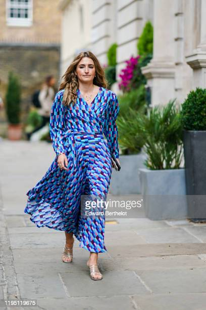 Guest wears a blue dress with printed patterns, during London Fashion Week September 2019 on September 16, 2019 in London, England.