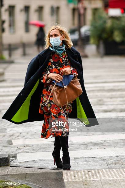 A guest wears a blue face mask a black coat with neon yellow inner lining a red and orange floral print dress a brown leather bag black high heeled...