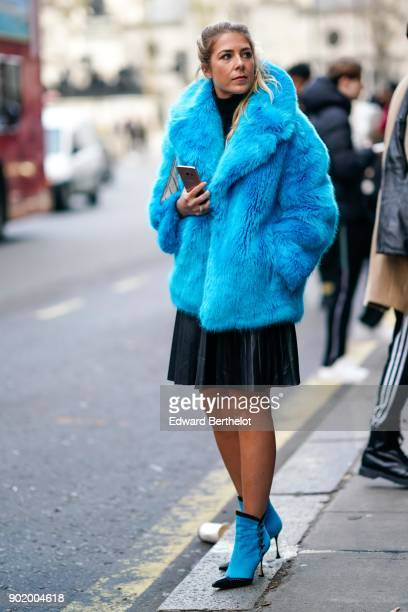 A guest wears a blue faux fur coat a black pleated skirt and is holding a smartphone during London Fashion Week Men's January 2018 at on January 6...