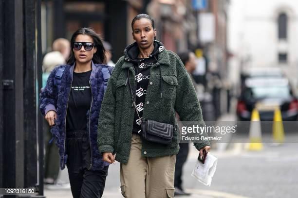 Guest wears a blue faux fur fluffy jacket ; a guest wears a black hoodie with a green fluffy jacket, during London Fashion Week Men's January 2019 on...