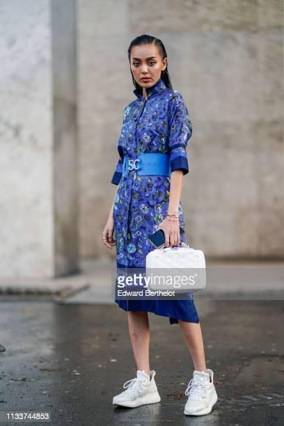 A guest wears a blue floral print dress a large SC belt a white bag sneakers outside Shiatzy Chen during Paris Fashion Week Womenswear Fall/Winter...