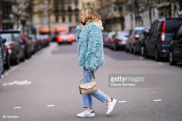 A guest wears a blue fluffy coat a JW Anderson bag blue jeans white sneakers during London Fashion Week February 2018 on February 18 2018 in London...