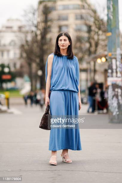 Guest wears a blue gathered sleeveless top, a blue flowing skirt, a brown woven handbag, white sandals, outside Ann Demeulemeester, during Paris...