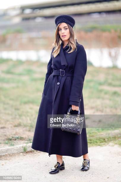 A guest wears a blue hat with lace a Lady Dior bag a dark blue coat black leather shoes outside Dior during Paris Fashion Week Womenswear...