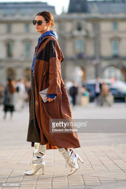 A guest wears a blue hoodie a brown coat silver boots outside Louis Vuitton during Paris Fashion Week Womenswear Spring/Summer 2018 on October 3 2017...