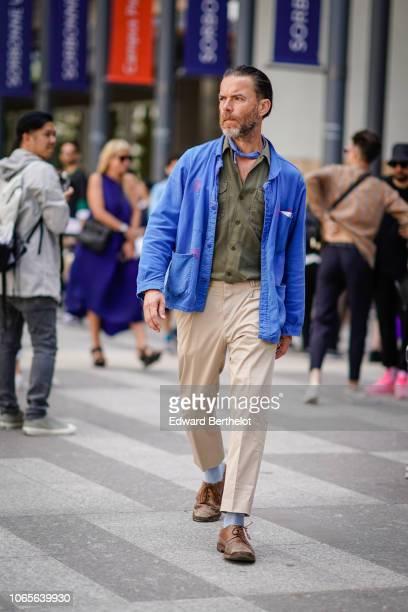 A guest wears a blue jacket a green khaki shirt beige pants brown shoes outside Issey Miyake during Paris Fashion Week Menswear SpringSummer 2019 on...